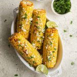 Four ears of air fried corn in a white dish and topped with feta and parsley.