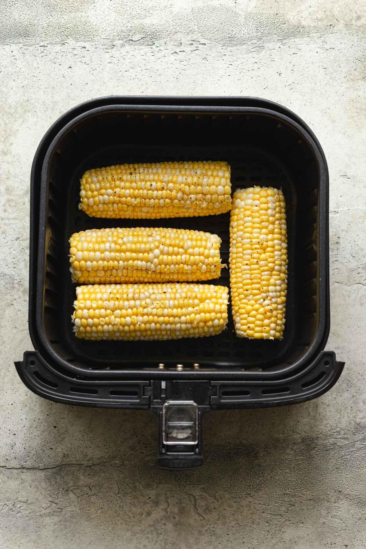 Four ears of raw, fresh corn arranged in an air fryer basket.