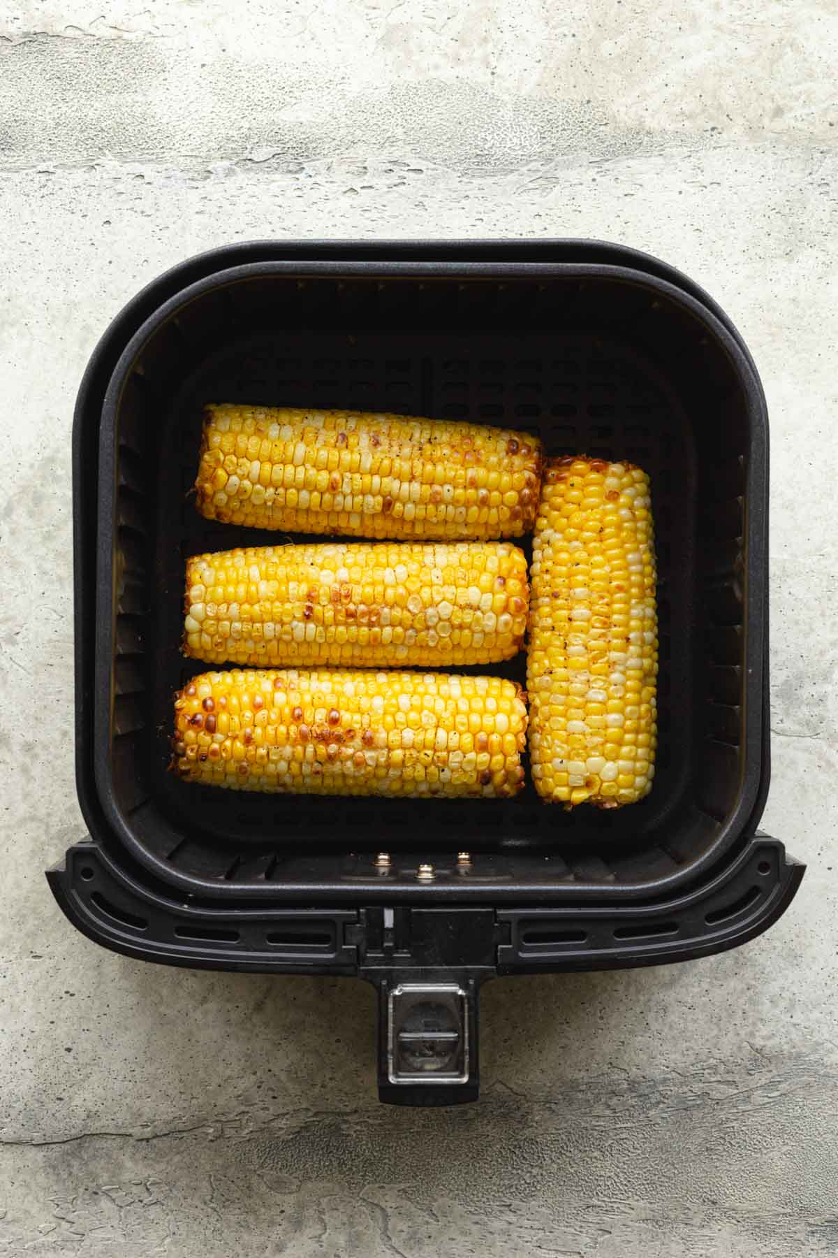 Four ears of fully cooked corn in an air fryer basket.