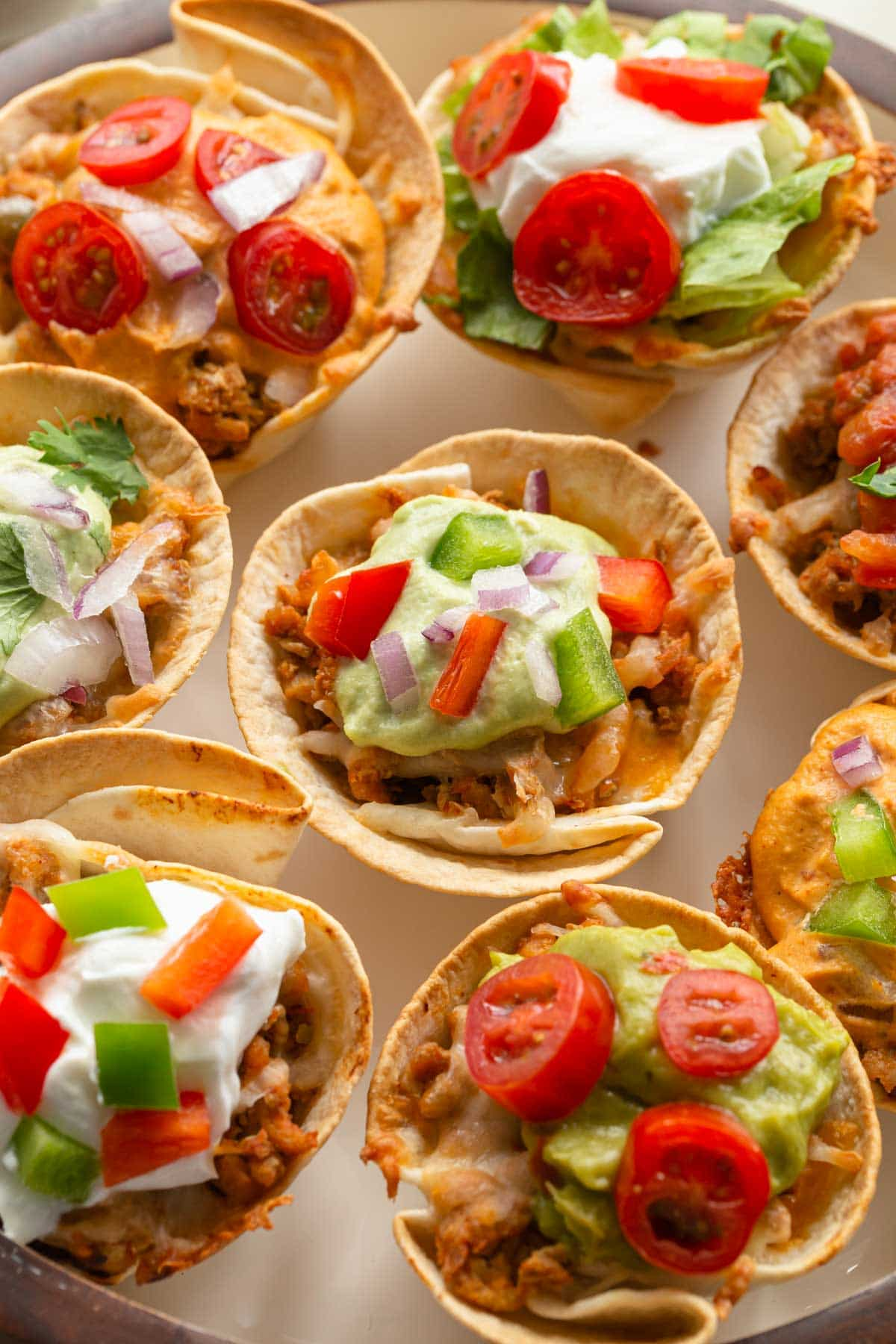 Up close view of mini taco cups with toppings, arranged on a plate.