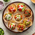 Overhead view of taco cups arranged on a round plate with a variety of toppings.