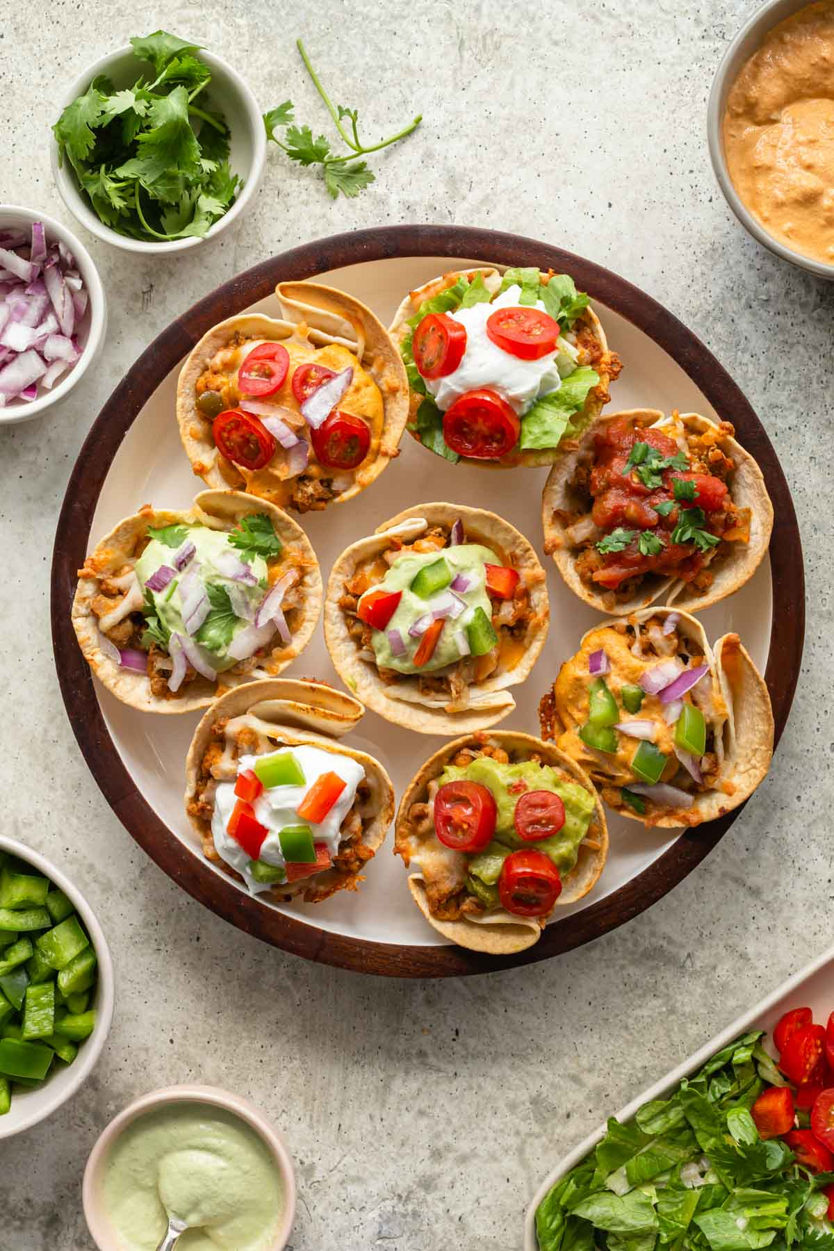 Overhead view of taco cups arranged on a round plate with toppings surrounding it.