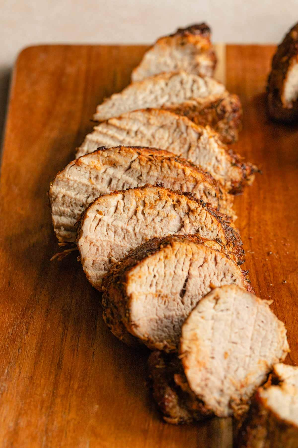 Side view of pork tenderloin slices on a wooden cutting board.
