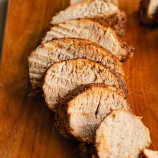 Close up side view of slices of pork tenderloin on a wooden board.