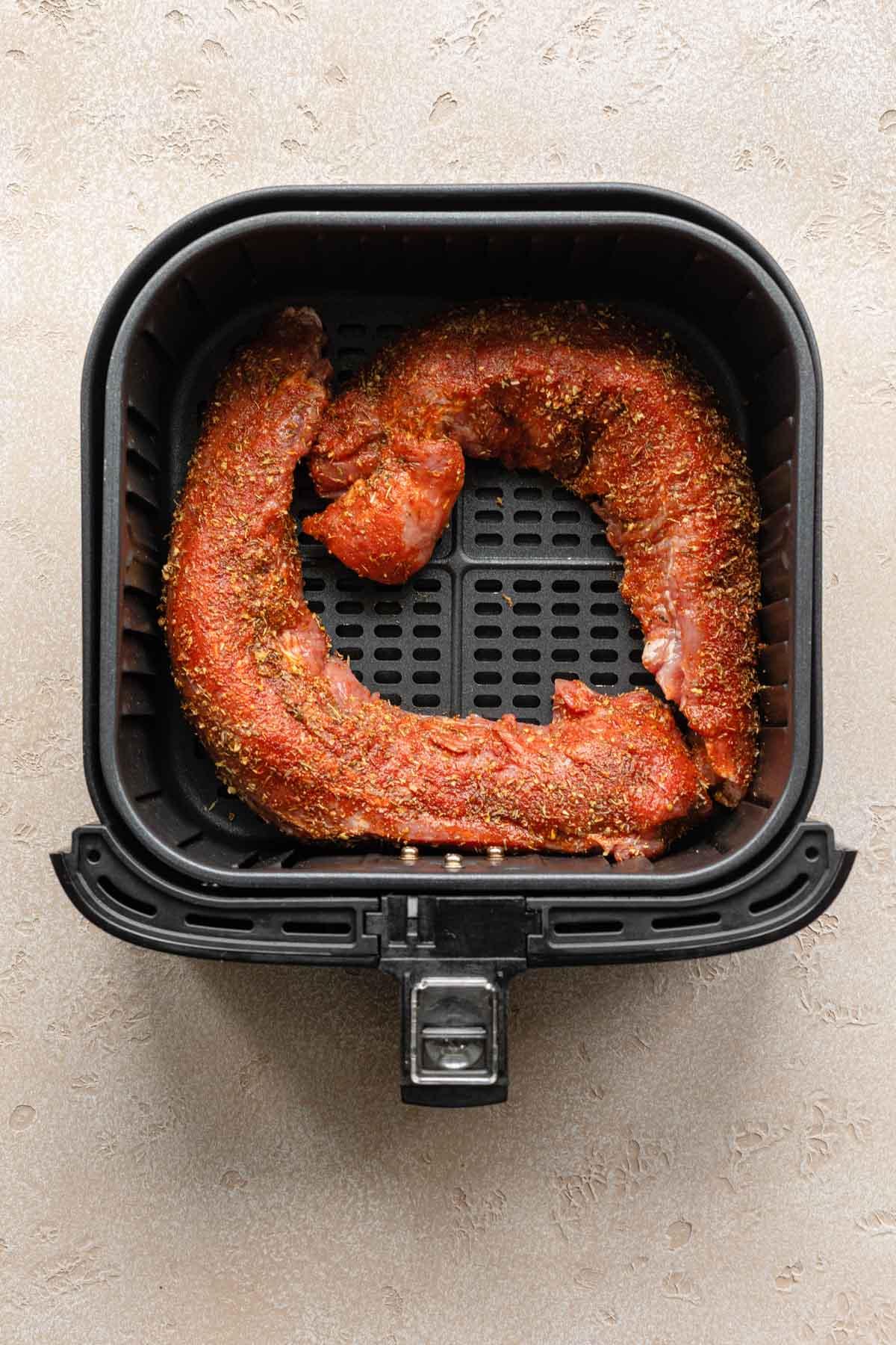 Two seasoned pork tenderloins in an air fryer basket.
