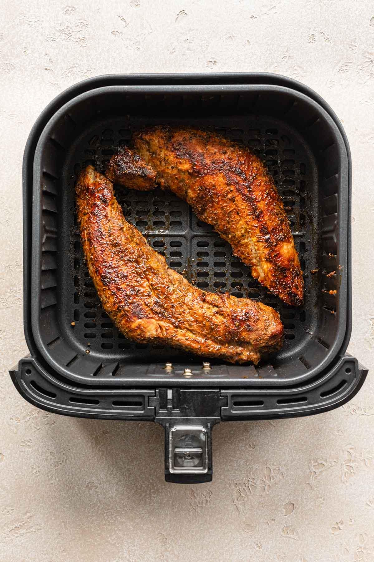 Two cooked pork tenderloins in an air fryer basket.
