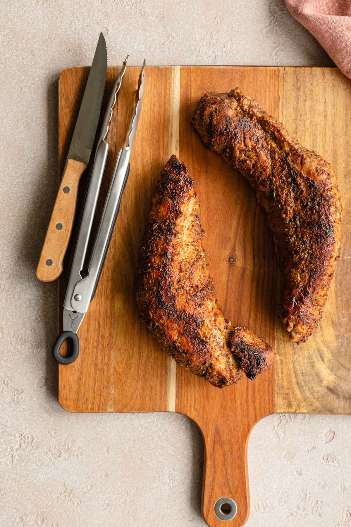 Two pork tenderloins on a wooden cutting board next to tongs and a knife.