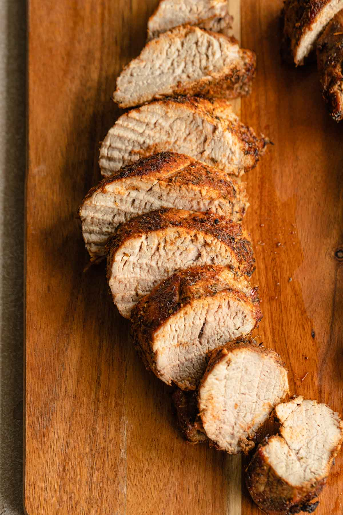 Close up view of pork tenderloin slices on a wooden board.