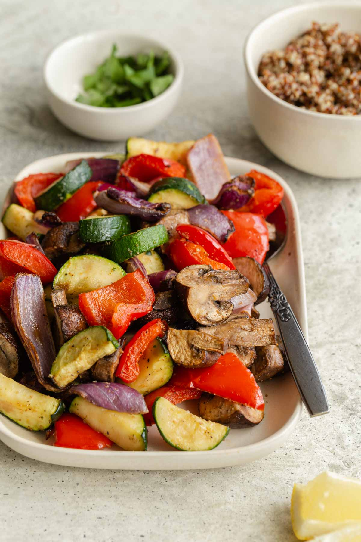 Side view of air fried vegetables on a plate with a spoon with quinoa and parsley in the background.