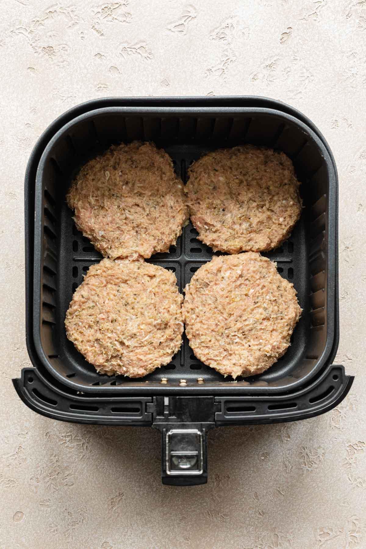Four turkey burger patties in an air fryer basket.