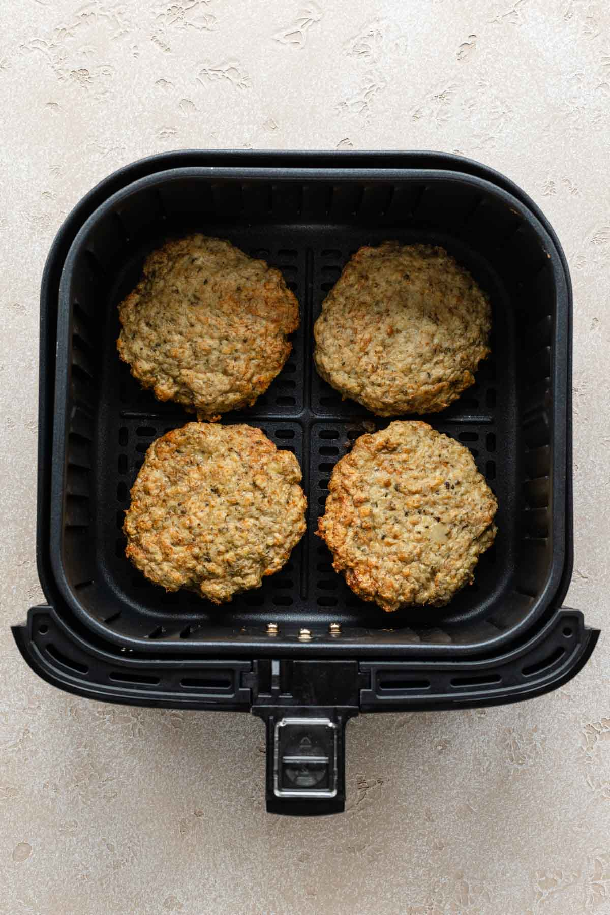 Four turkey burgers cooked in an air fryer basket.