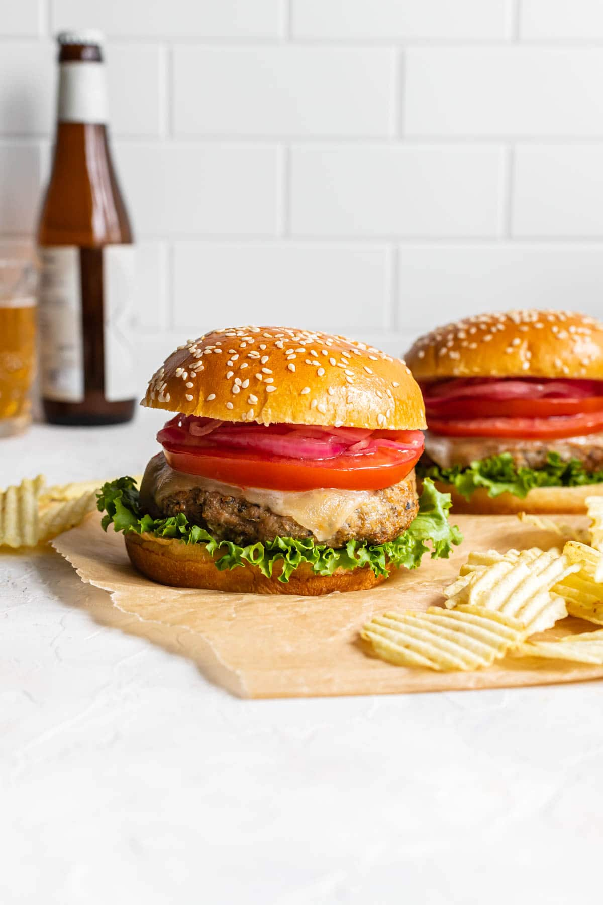 Side view of two burgers on parchment paper with potato chips and a bottle of beer in the background.