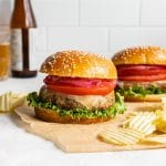 Air fryer turkey burgers arranged on a sheet of brown parchment paper with potato chips on the side.
