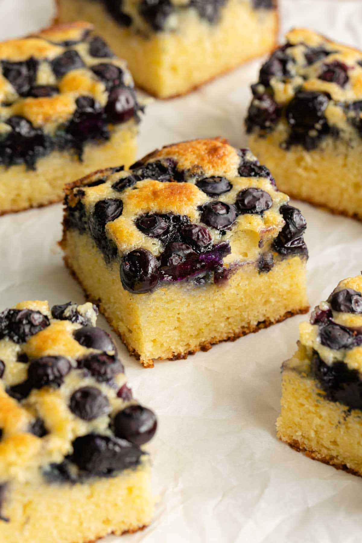 Lemon blueberry cake cut into squares and arranged on a sheet of parchment paper.