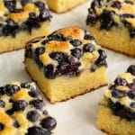 Blueberry cake cut into squares and arranged on parchment paper.