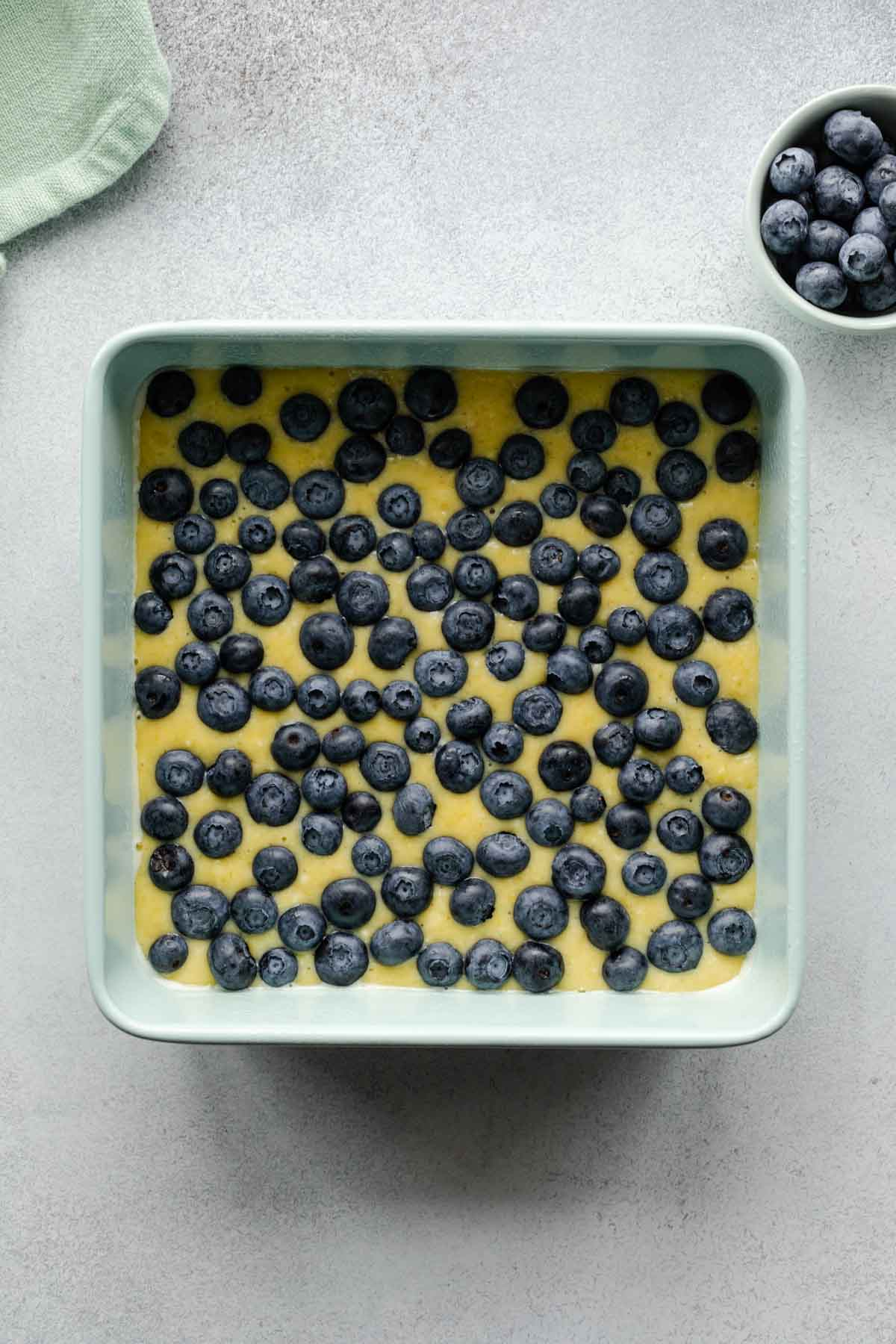 Cake batter in a square pan with blueberries arranged on top.