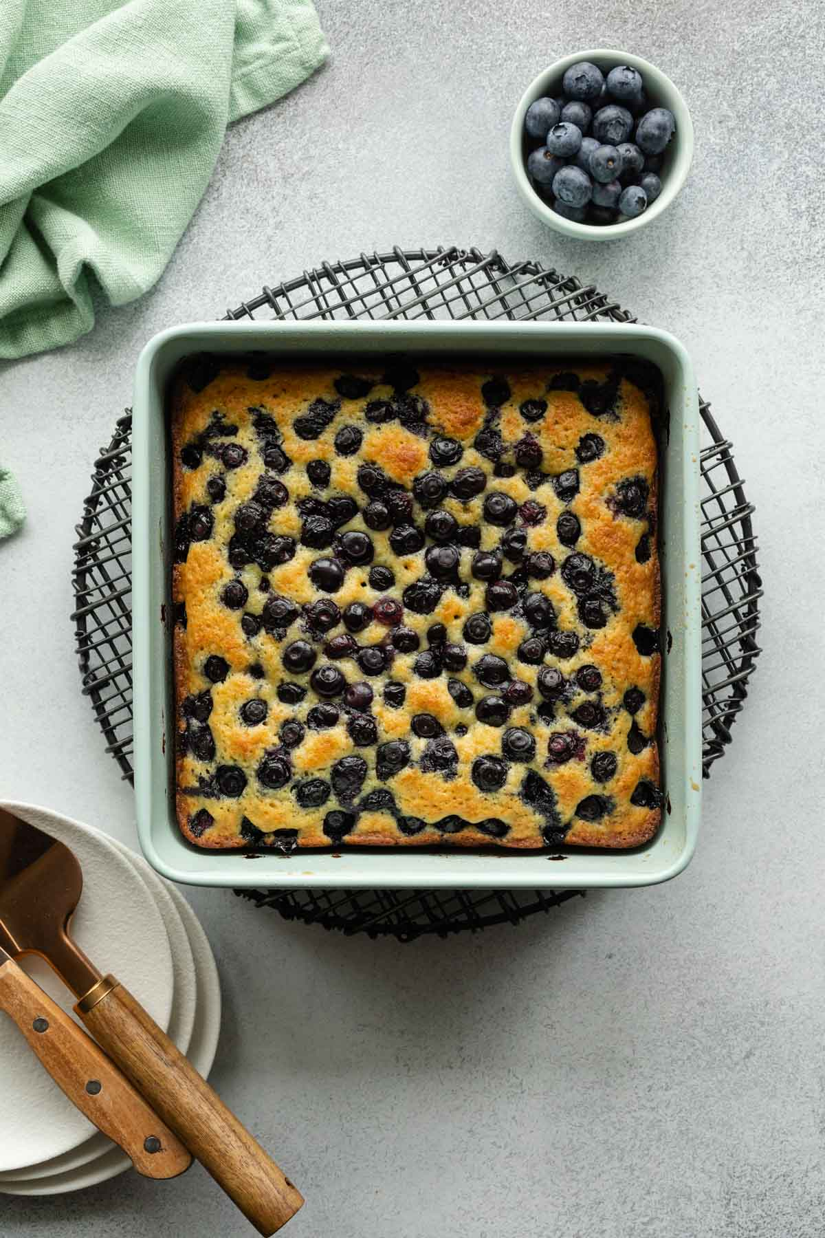 Overhead view of blueberry cake cooling on a wire rack.
