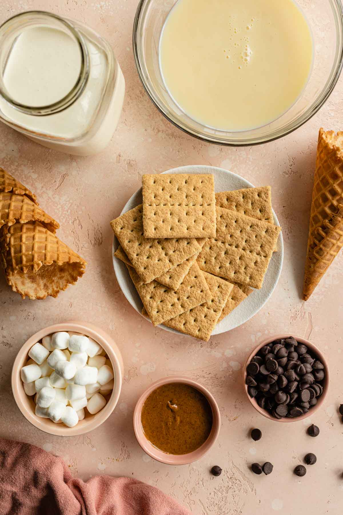 Ingredients to make s'mores ice cream arranged individually on a pink surface.