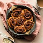 Overhead view of air fried cinnamon rolls in a round cake pan.