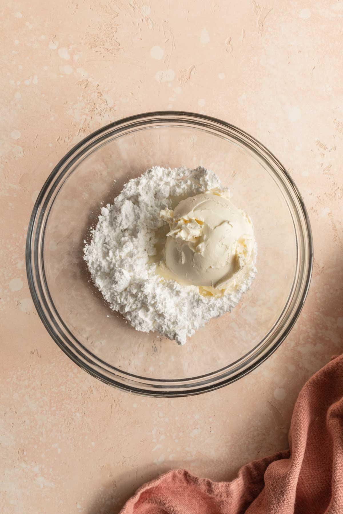 Powdered sugar and cream cheese in a glass bowl to make the frosting.
