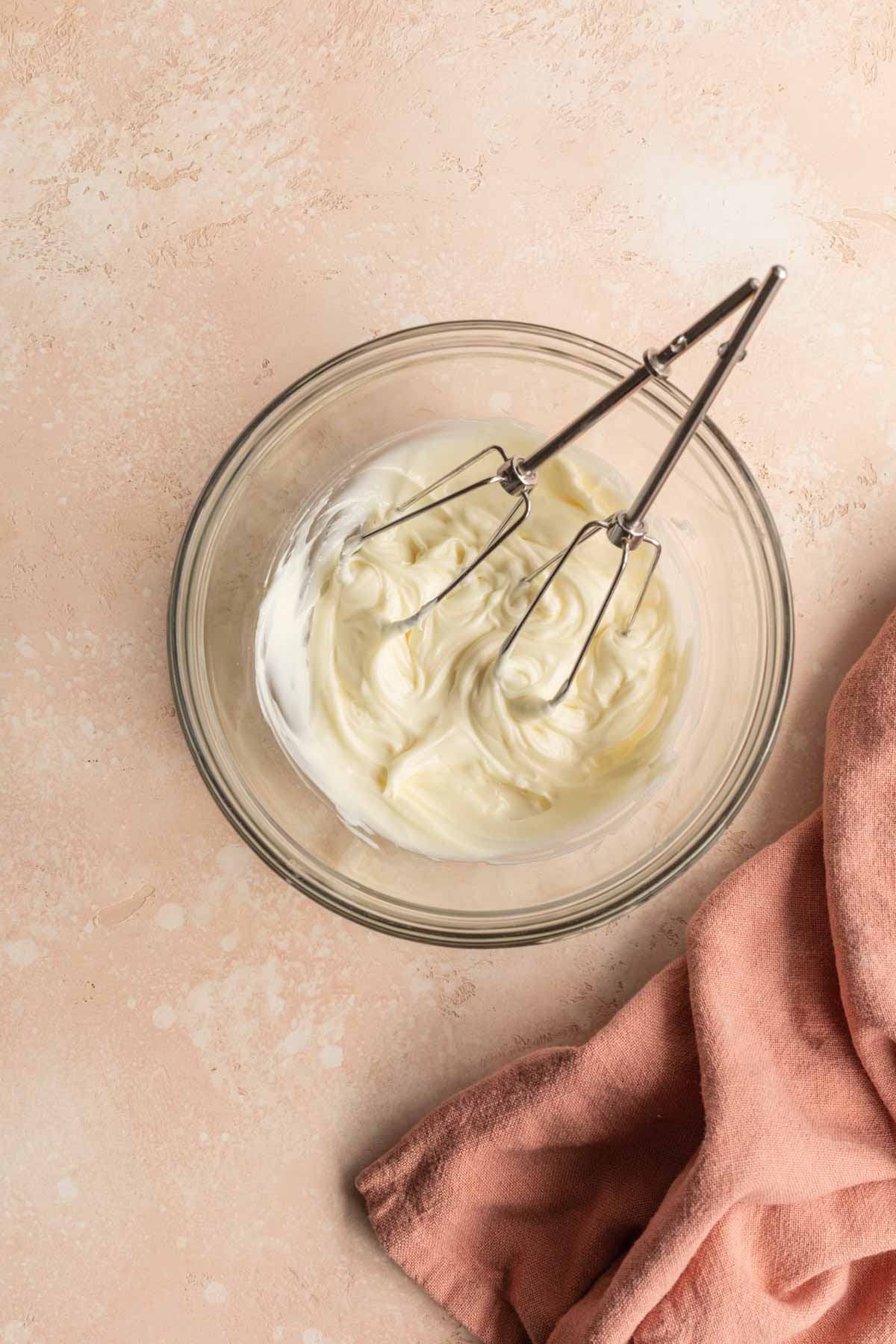 Cream cheese frosting in a glass bowl.