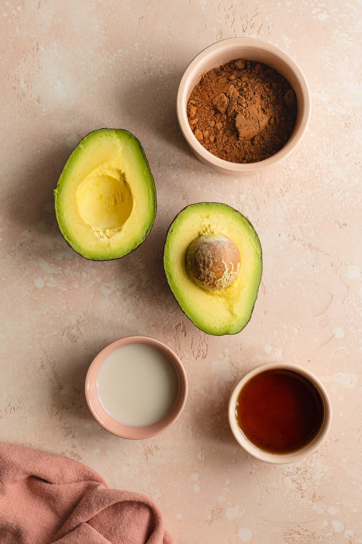 Ingredients to make chocolate avocado frosting arranged individually.