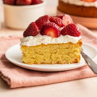 Slice of lemon almond flour cake on a white plate and topped with whipped cream and strawberries.