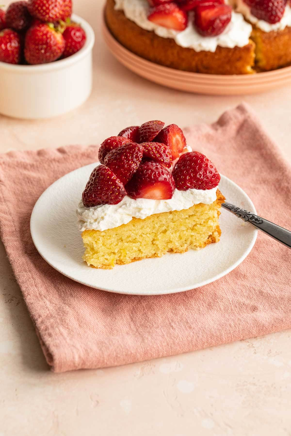 Slice of almond flour cake on a white plate and topped with strawberries and whipped cream.