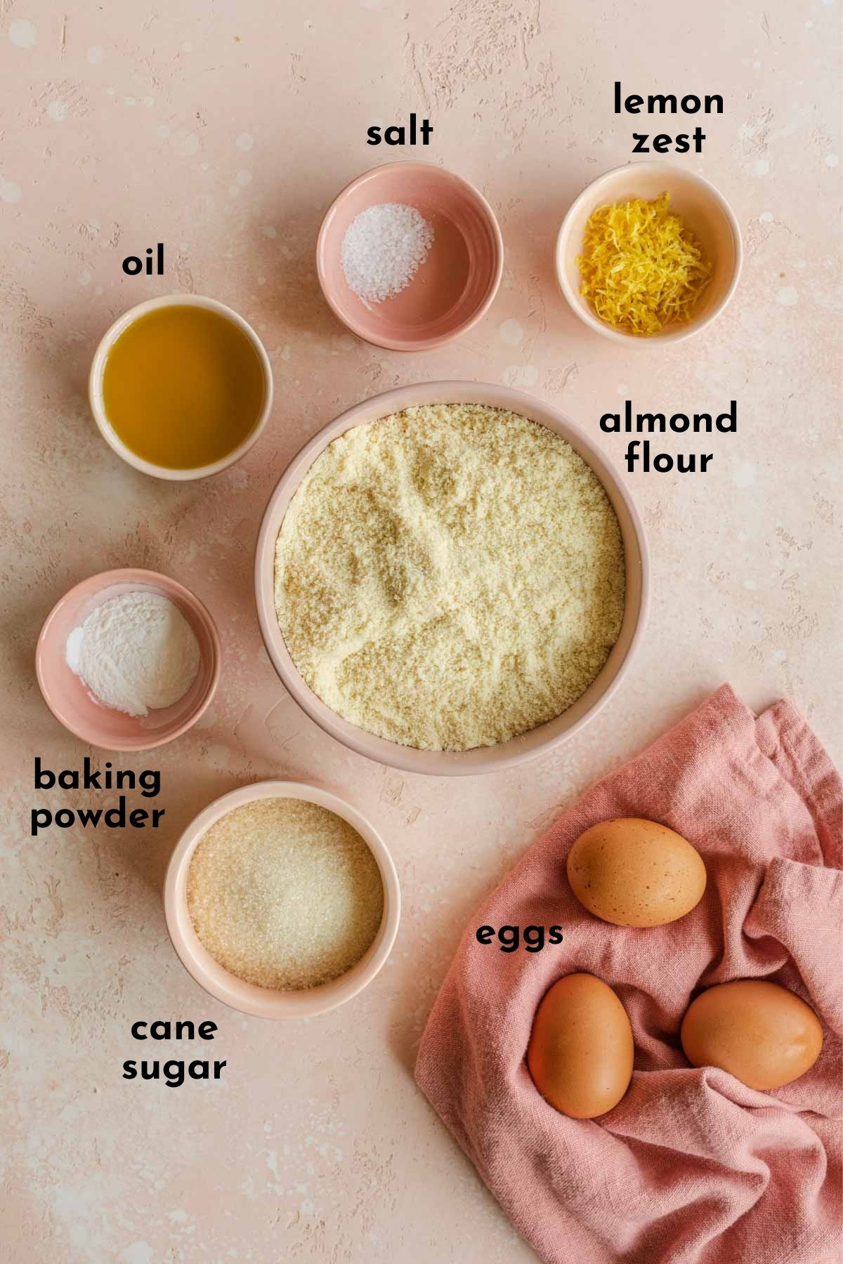 Ingredients for almond flour cake arranged individually and labelled.