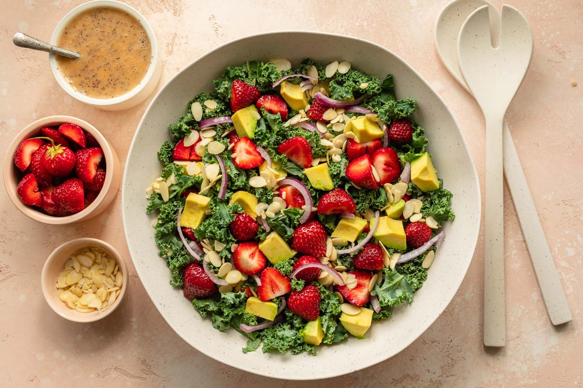 Strawberry avocado kale salad in a large white bowl with poppyseed dressing on the side.