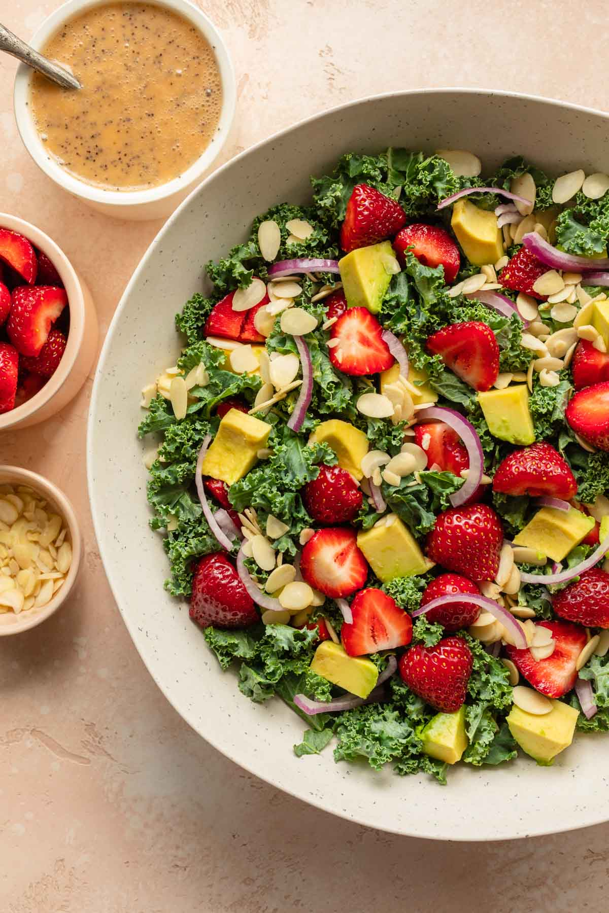 Overhead of strawberry kale salad in a large white bowl with poppyseed dressing in a side bowl.