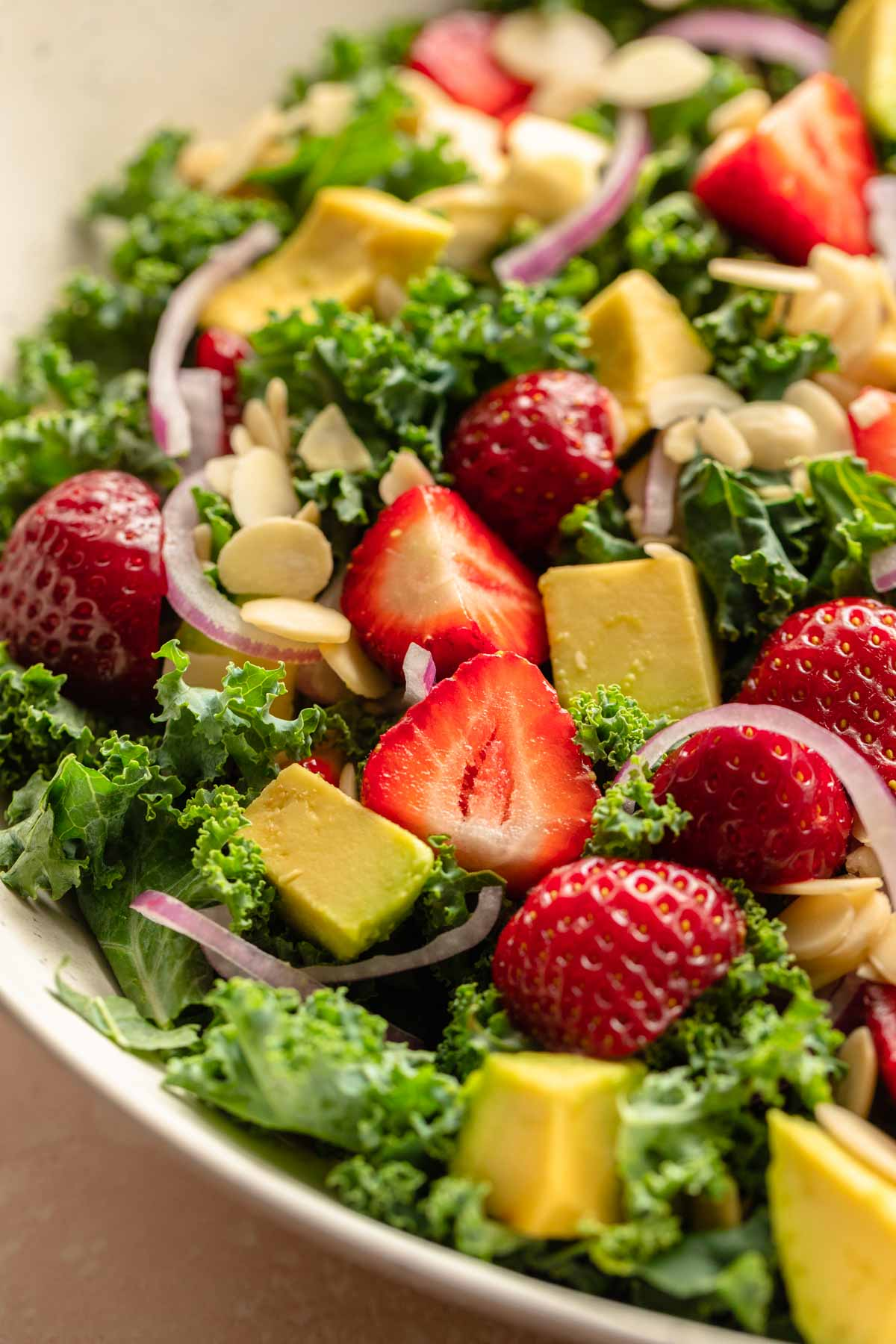 Close up of chopped strawberries and avocado on top of a kale salad.