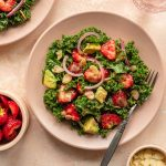 Strawberry kale salad on a pink plate.