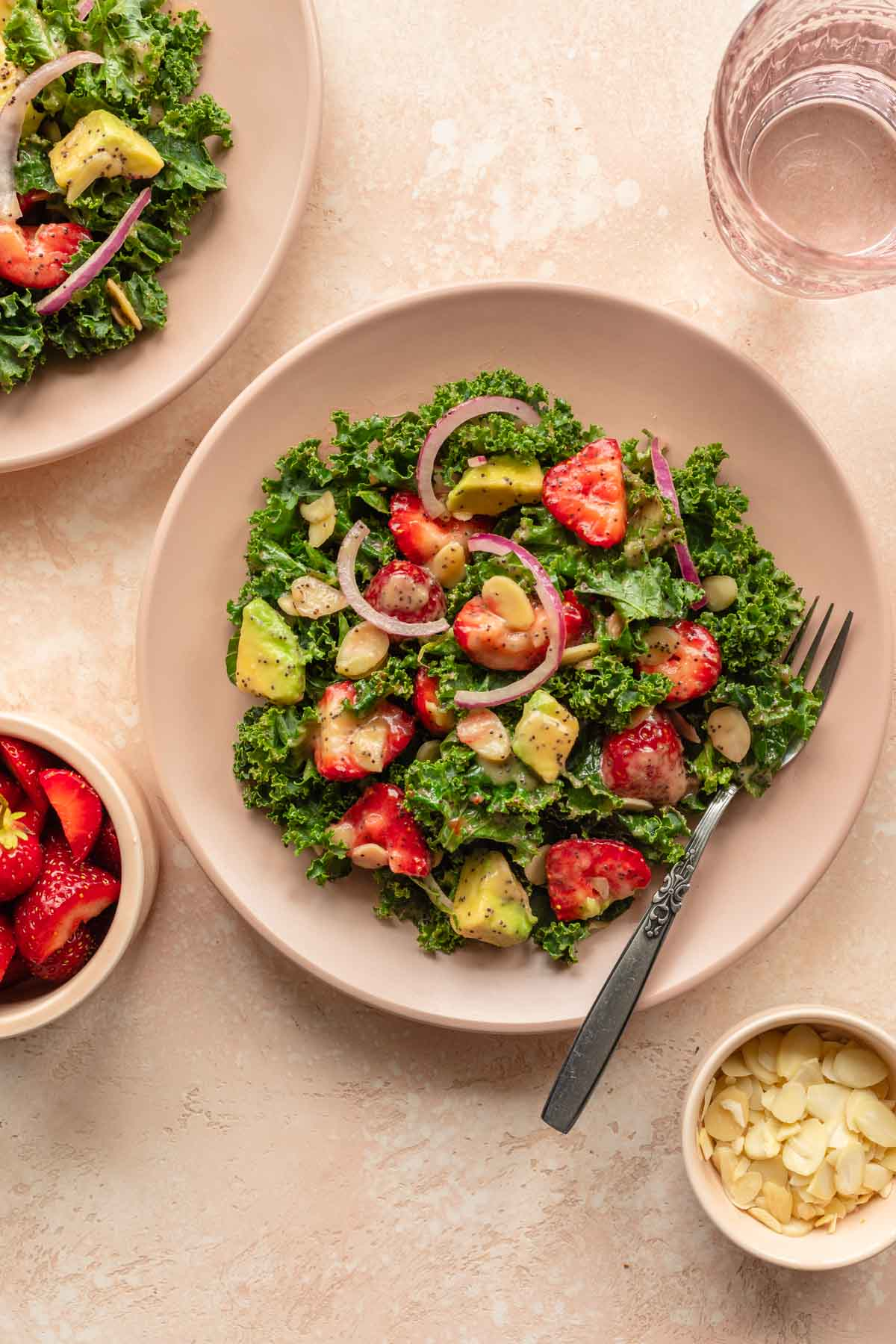 Overhead of kale strawberry salad on a pink plate with a fork.