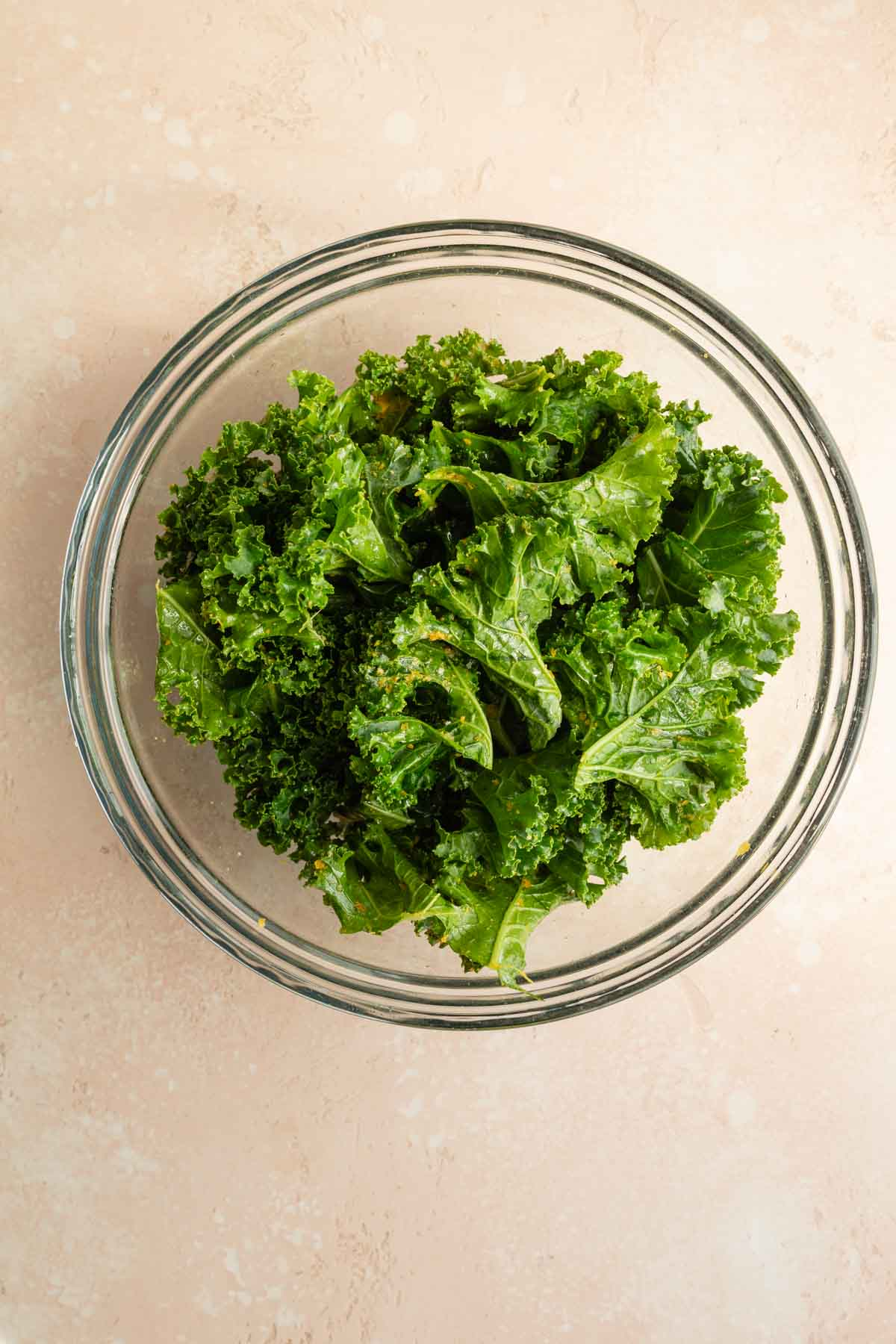 Torn and seasoned pieces of kale in a glass bowl.