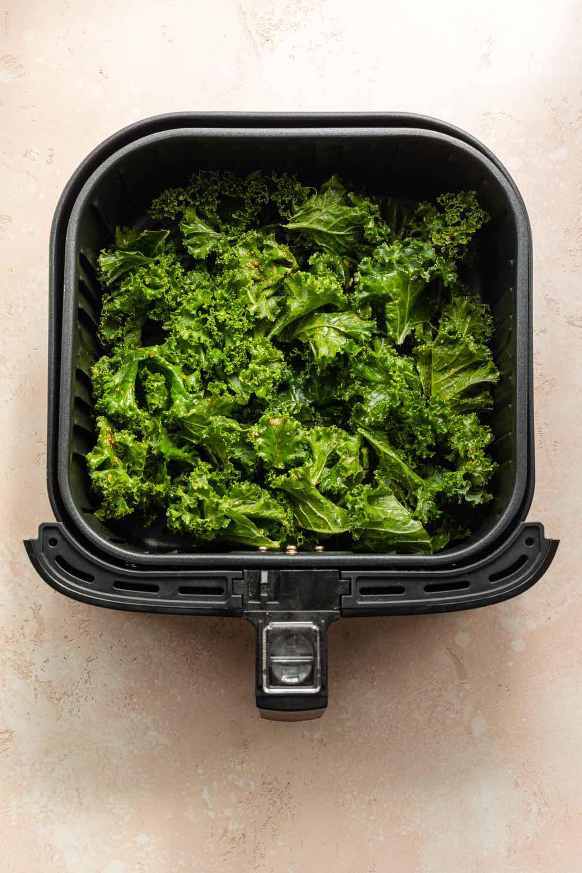 Overhead view of seasoned kale pieces in an air fryer basket.