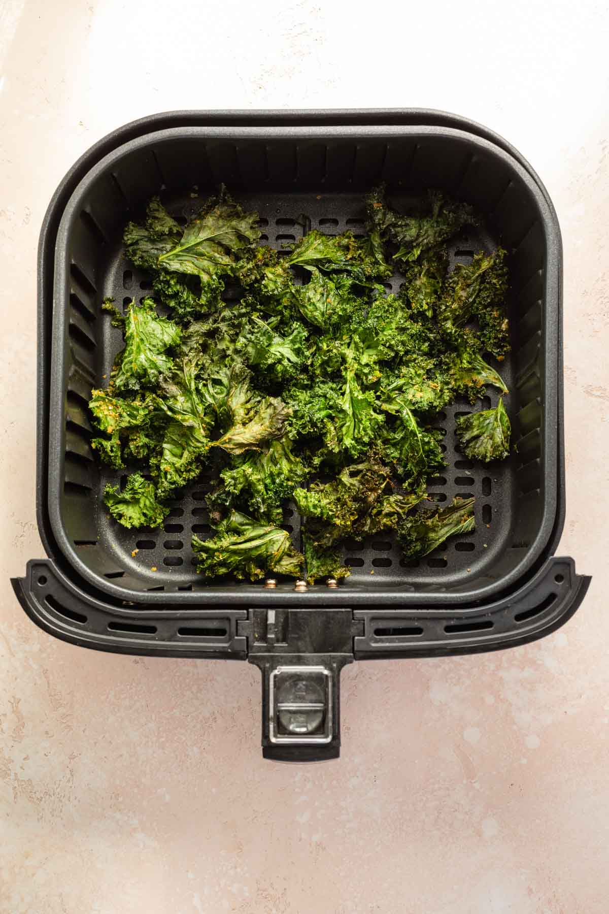 Overhead view of air fried kale chips in an air fryer basket.