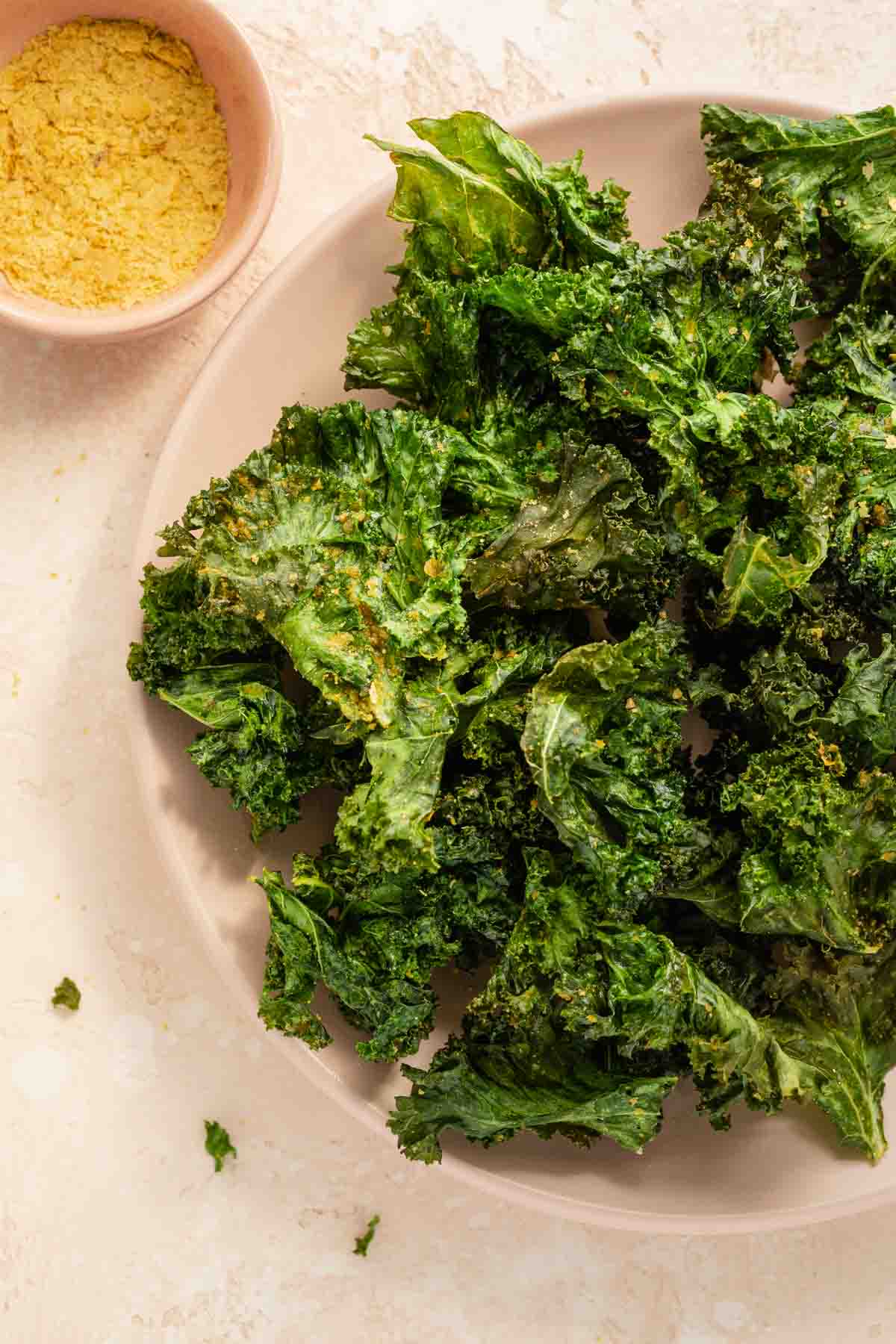 Close up view of kale chips arranged on a plate.