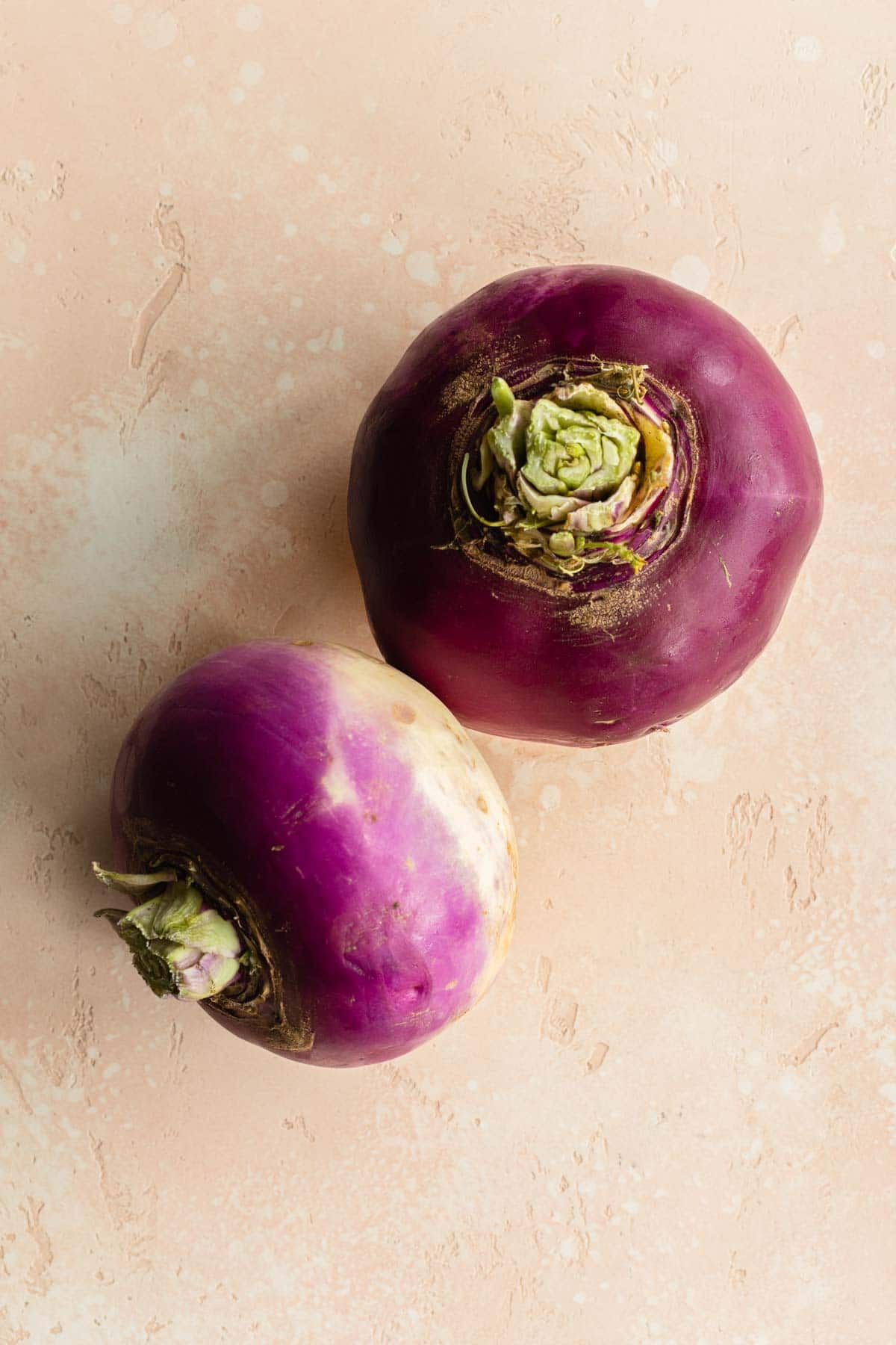 Two unpeeled turnips on a pink surface.
