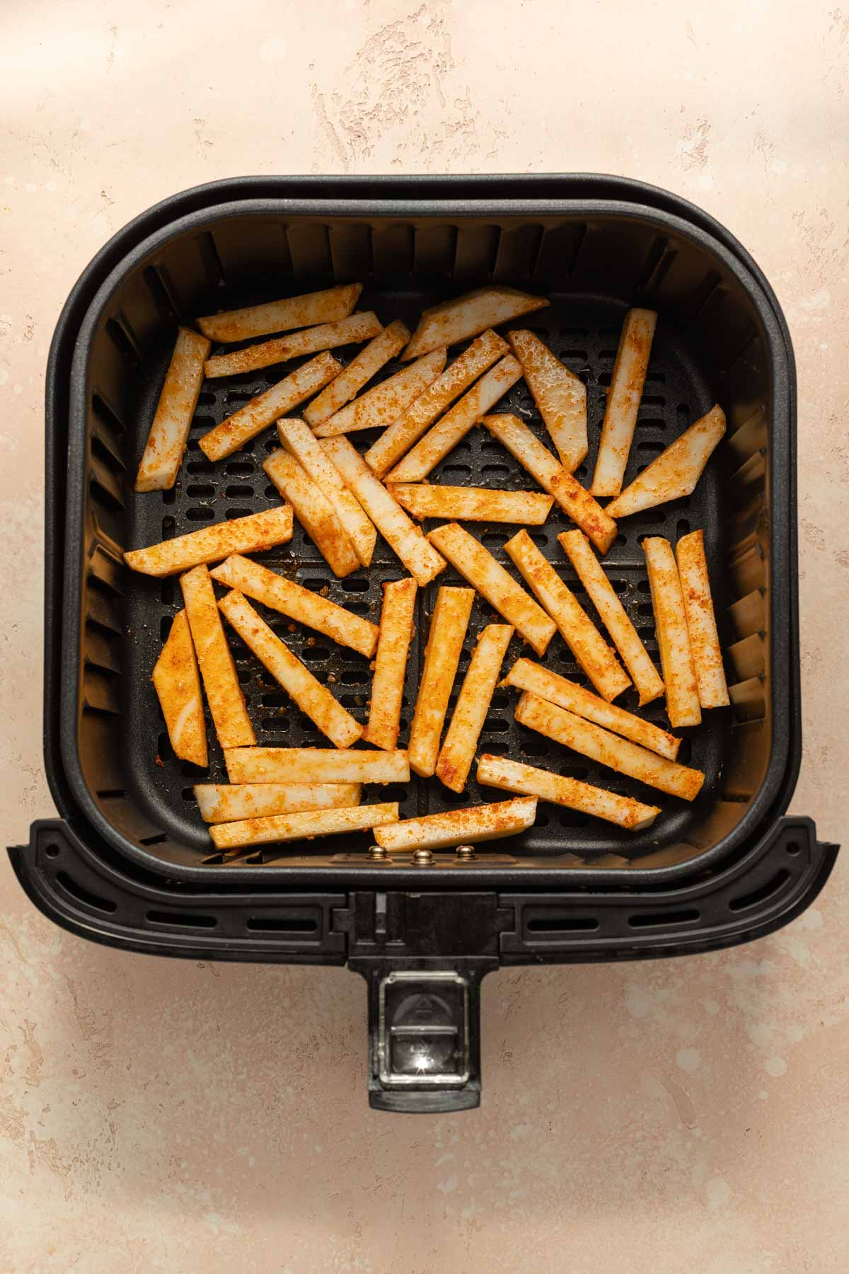Seasoned raw turnip fries arranged in a single layer in an air fryer basket.