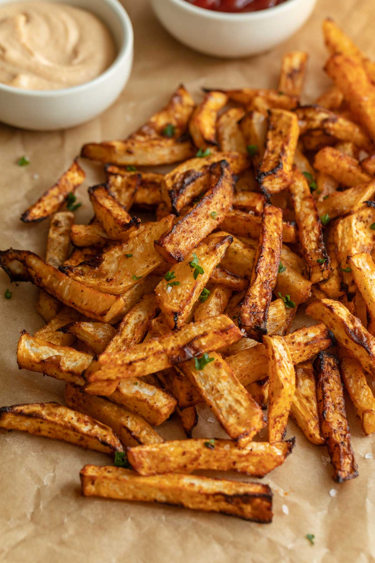 Close up of air fryer turnip fries with chopped parsley sprinkled on top.