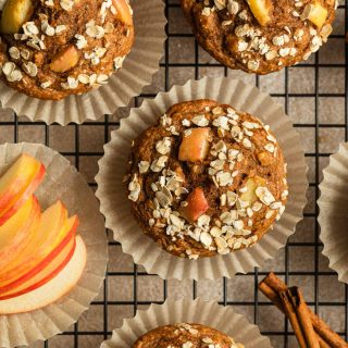 Apple spice muffins arranged in muffin liners on a cooling rack.