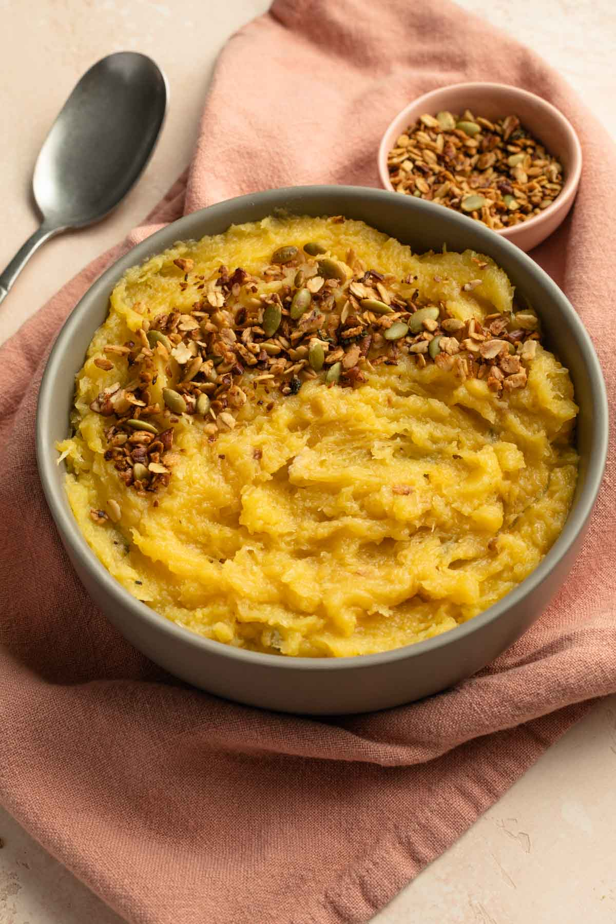 Side view of mashed squash topped with granola in a bowl.