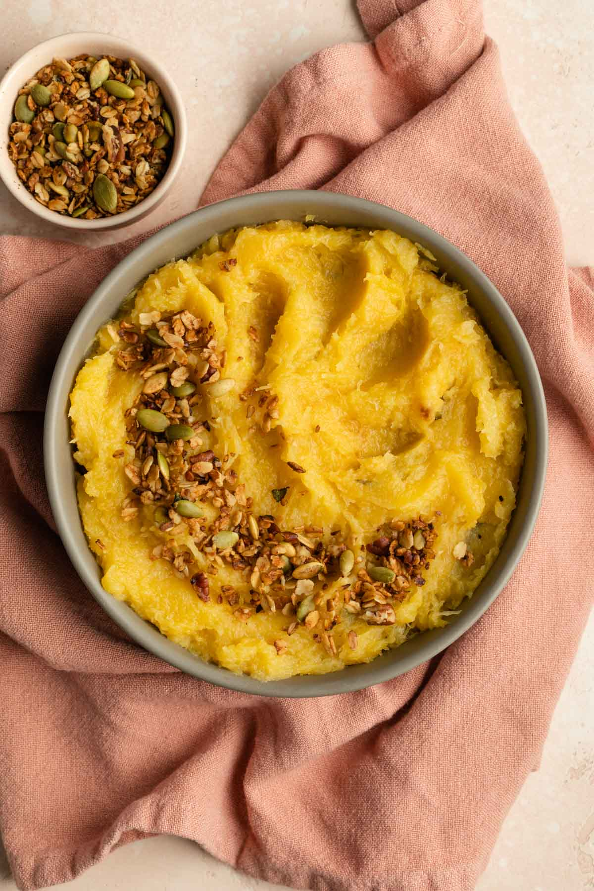 Acorn squash mash in a beige bowl and topped with savoury granola.