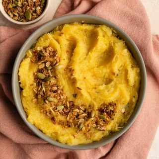 Mashed acorn squash in a bowl on a pink cloth with savoury granola on top.
