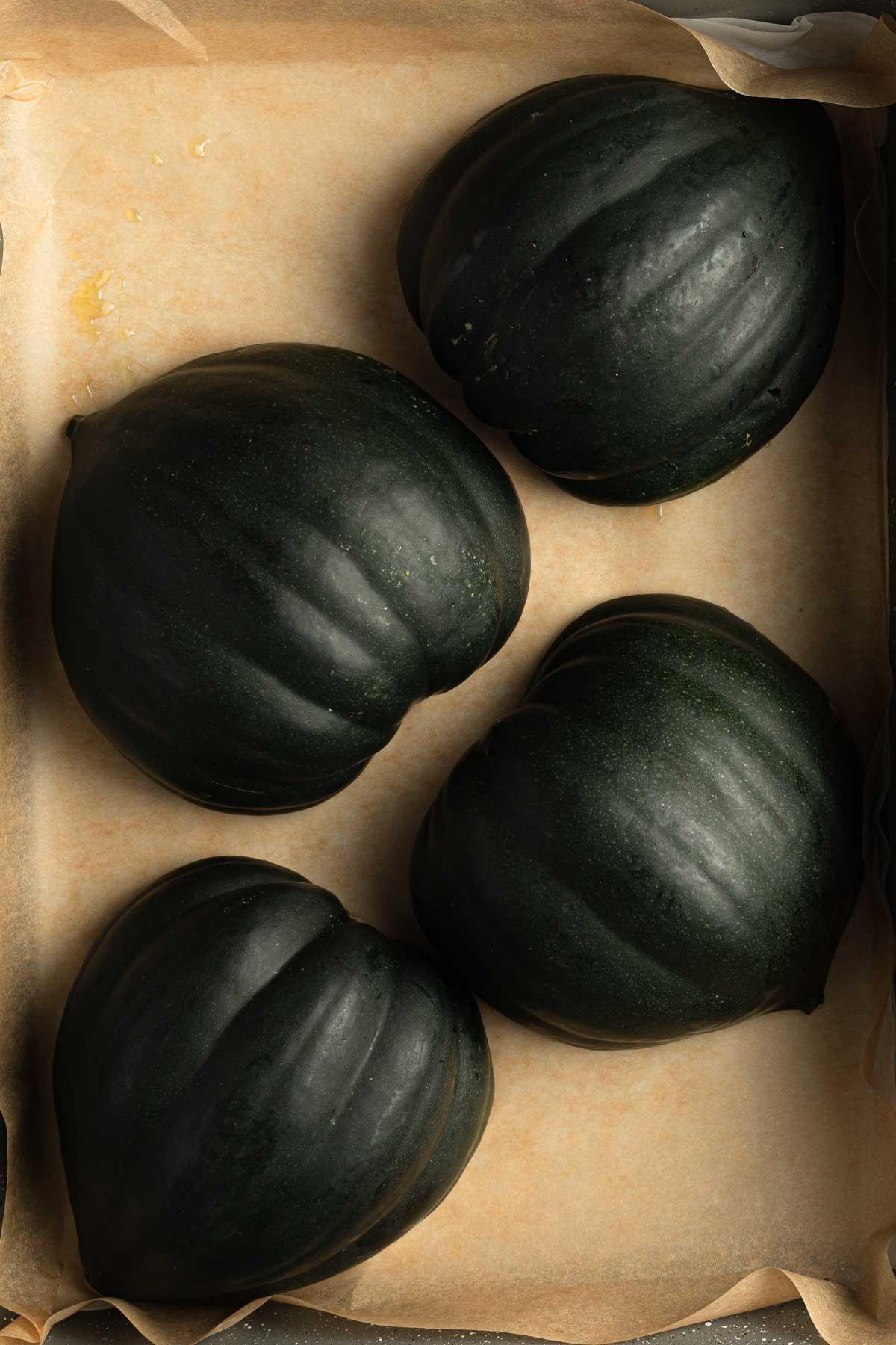 Acorn squash halves arranged cut side down in a roasting pan.