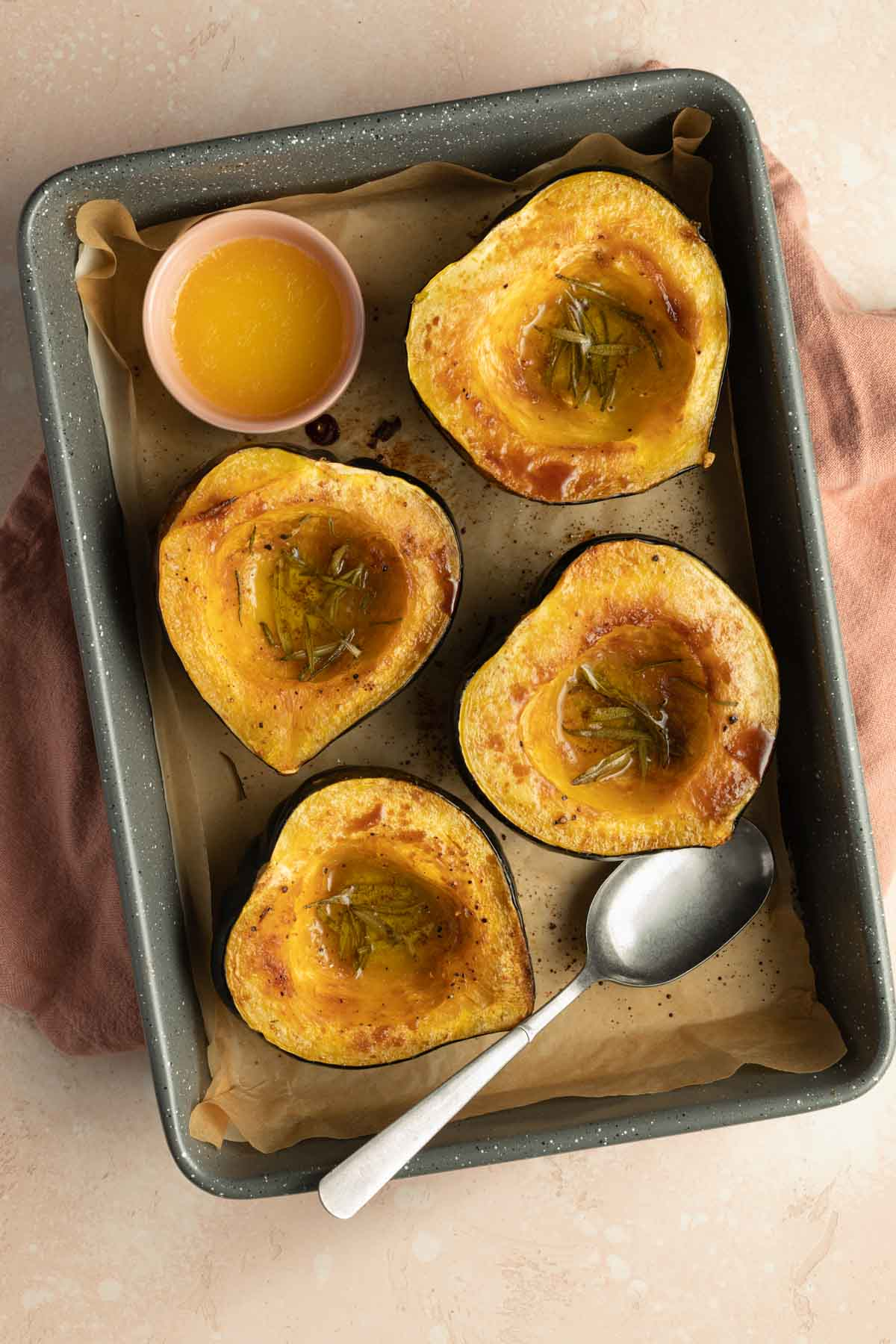 Roasted squash halves in a roasting pan.