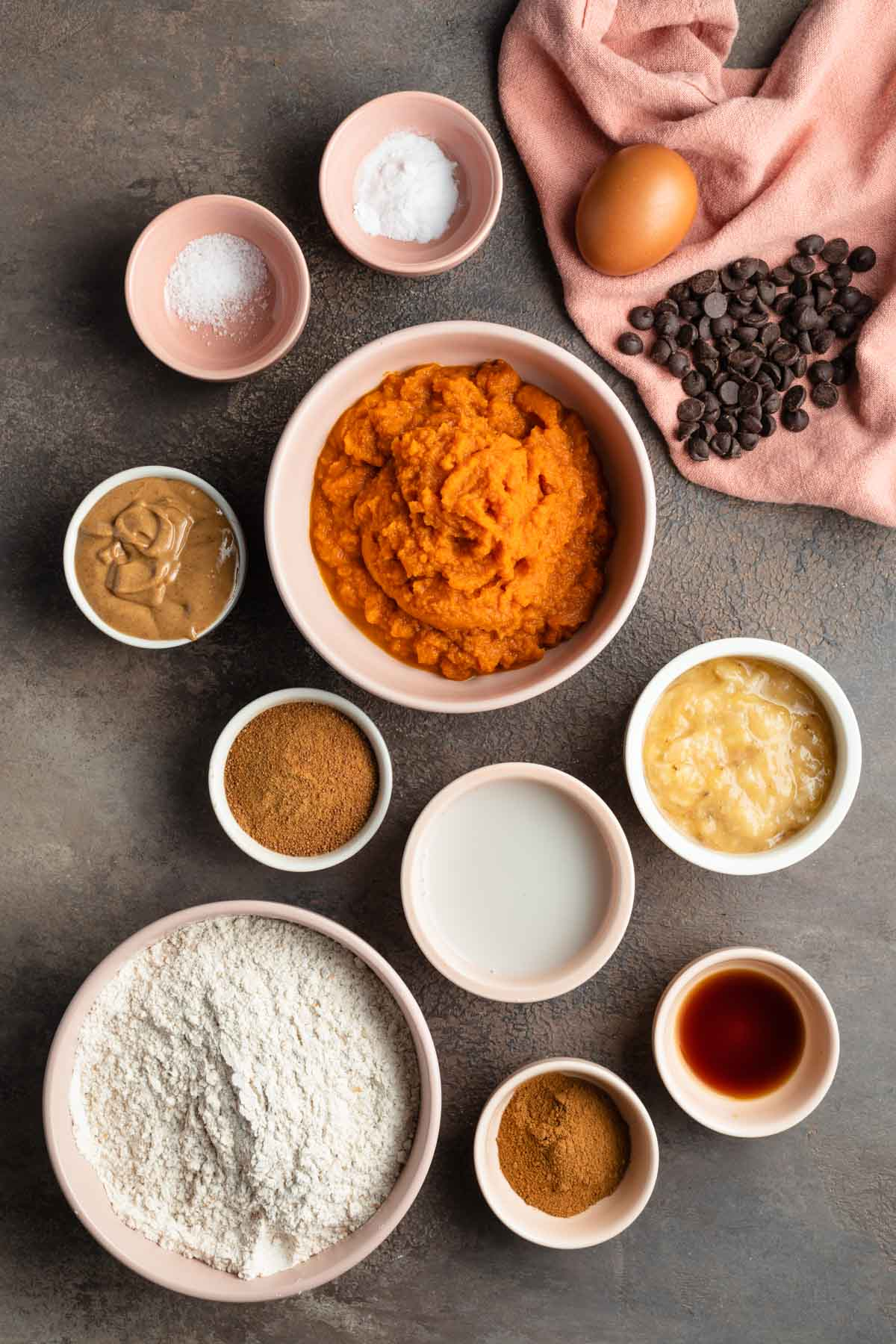 Ingredients to make whole wheat pumpkin muffins arranged in individual bowls.