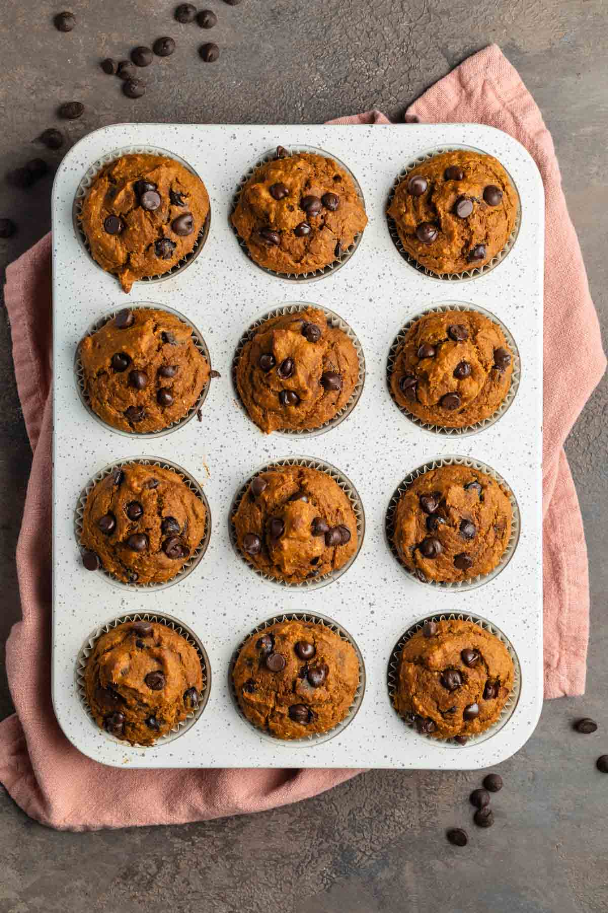 Pumpkin muffins baked up in a white muffin pan.