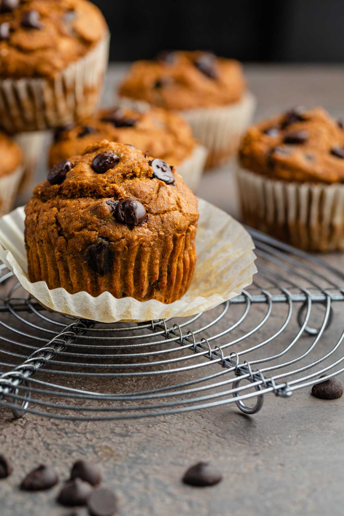 Side view of a whole wheat pumpkin muffin on a cooling rack.